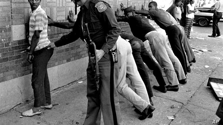 FILE - In this July 24, 1967, file photo, a Michigan State police officer searches a youth on Detroit's 12th Street where looting was still in progress after the previous day's rioting.