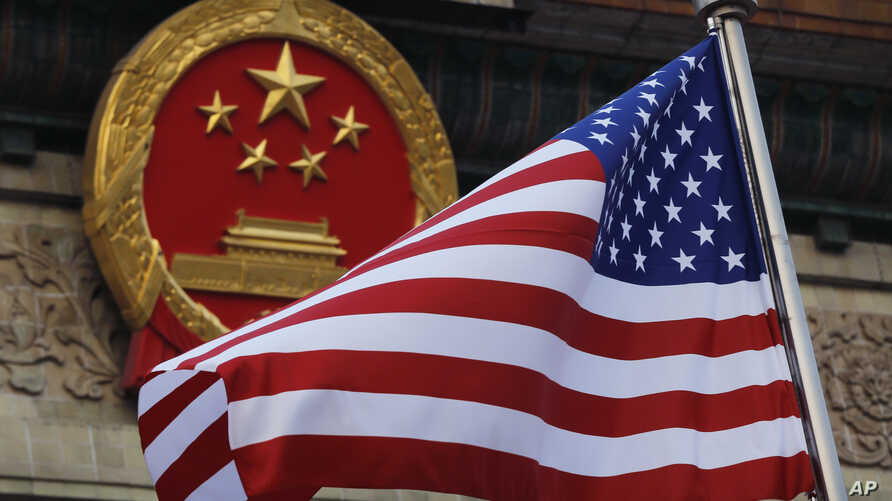 FILE - An American flag is flown next to the Chinese national emblem during a welcome ceremony for visiting U.S. President Donald Trump outside the Great Hall of the People in Beijing, Nov. 9, 2017. China has criticized a U.S. government report that