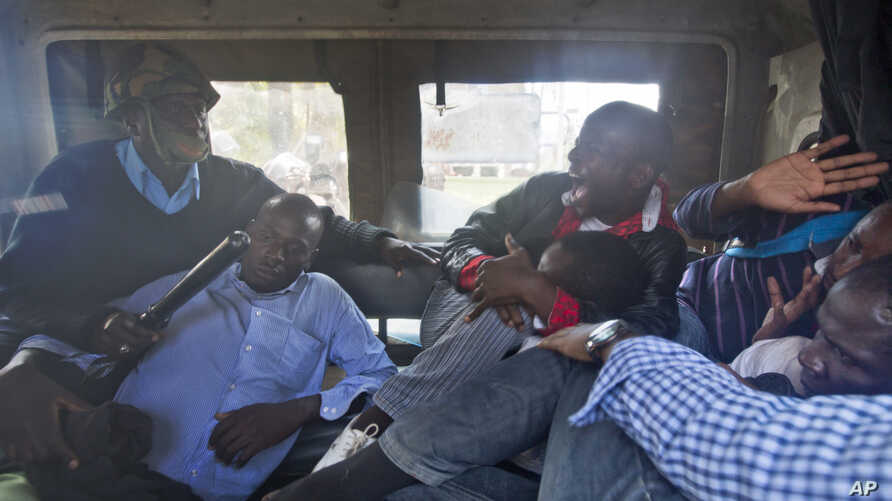 Protesters are beaten with wooden clubs inside the back of a police pickup truck after being arrested outside the Parliament building in Nairobi, Kenya Thursday, Dec. 18, 2014.