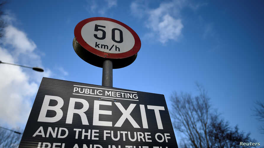 FILE - A Brexit sign is seen between Donegal in the Republic of Ireland and Londonderry in Northern Ireland at the border village of Muff, Ireland, Feb. 1, 2018.