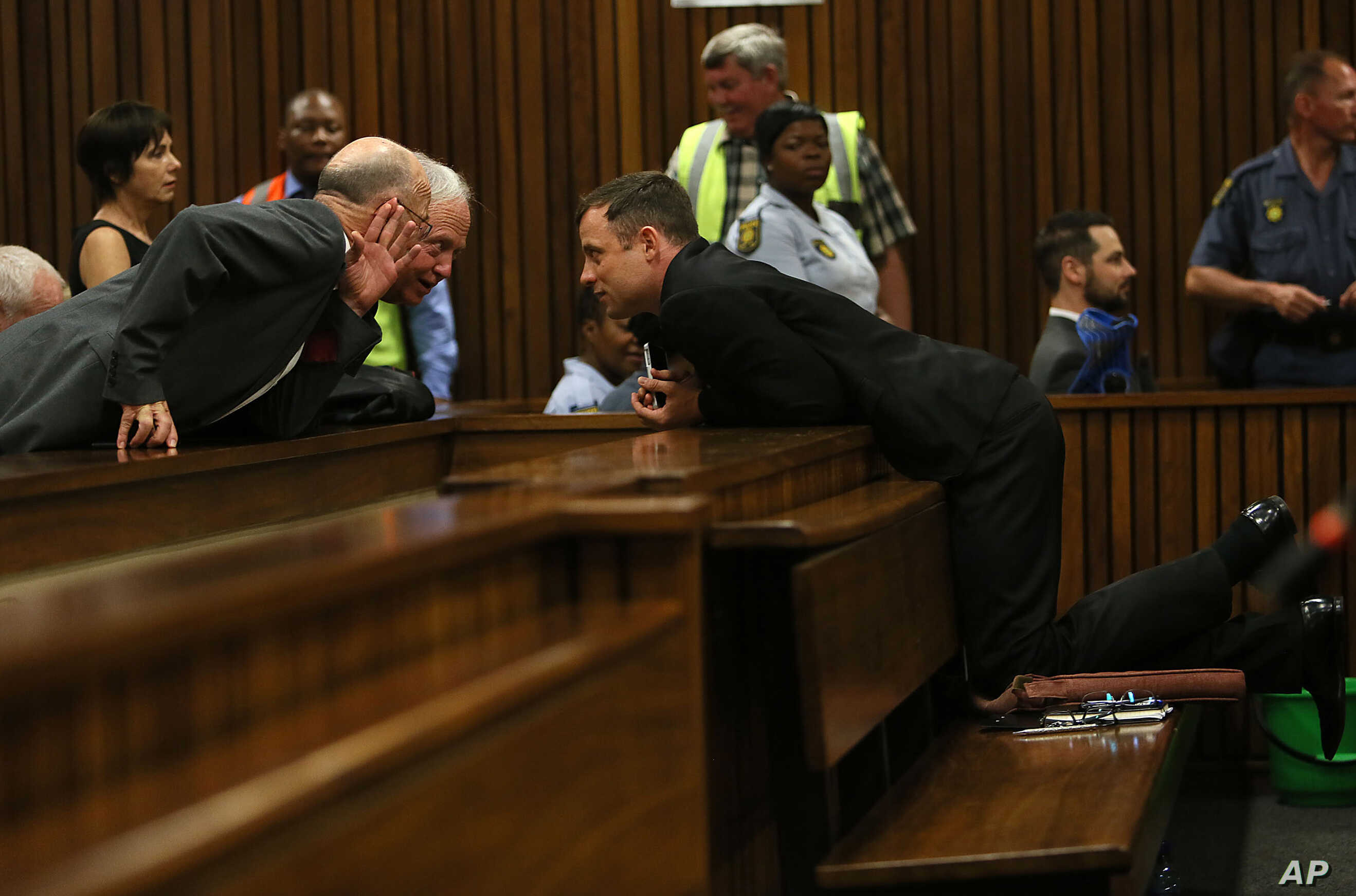 Oscar Pistorius, right, speaks with his uncle Arnold Pistorius, left, as he attends the fourth day of sentencing proceedings at the high court in Pretoria, South Africa, Oct. 16, 2014.