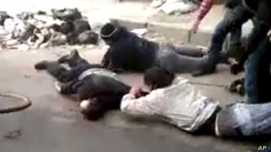 Men retrieve a body, in a rubbish-strewn street in Homs, Syria  December 15, 2011.