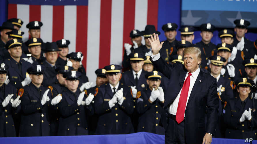 President Donald Trump waves after speaking to law enforcement officials on the street gang MS-13, July 28, 2017, in Brentwood, N.Y.