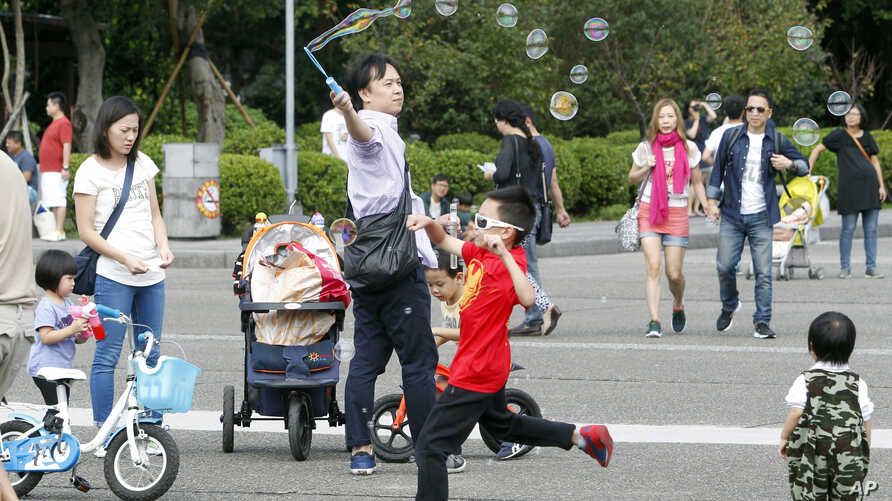 Taiwanese people enjoy their weekend, Nov. 20, 2016, at the Sun Yat-sen Memorial Hall in Taipei, Taiwan. Taiwan will soon start mandating two-day weekends for its workforce. The changed labor standards reflect desires for better work-life balance in