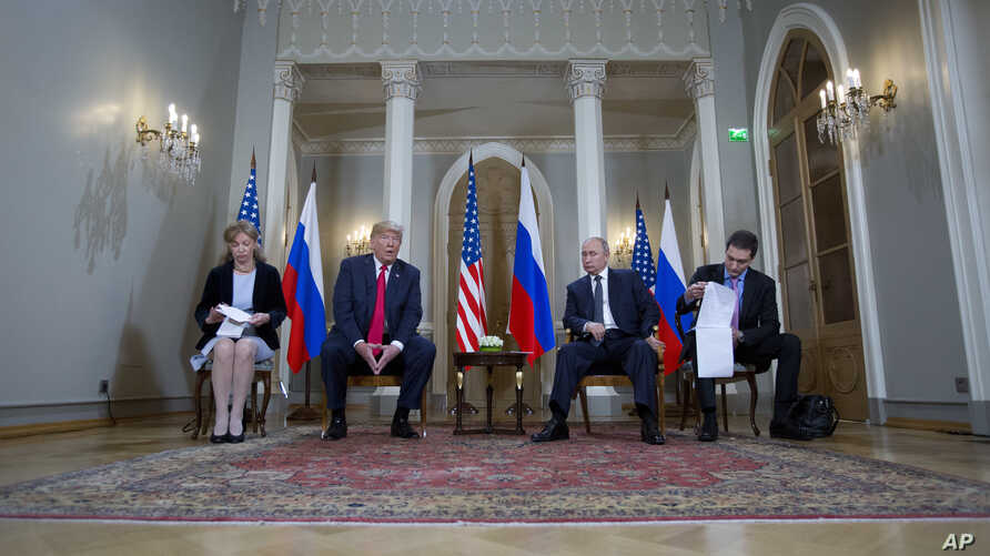 Russian President Vladimir Putin, right, and U.S. President Donald Trump, left, with their interpreters at the beginning of their meeting at the Presidential Palace in Helsinki, Finland, July 16, 2018.