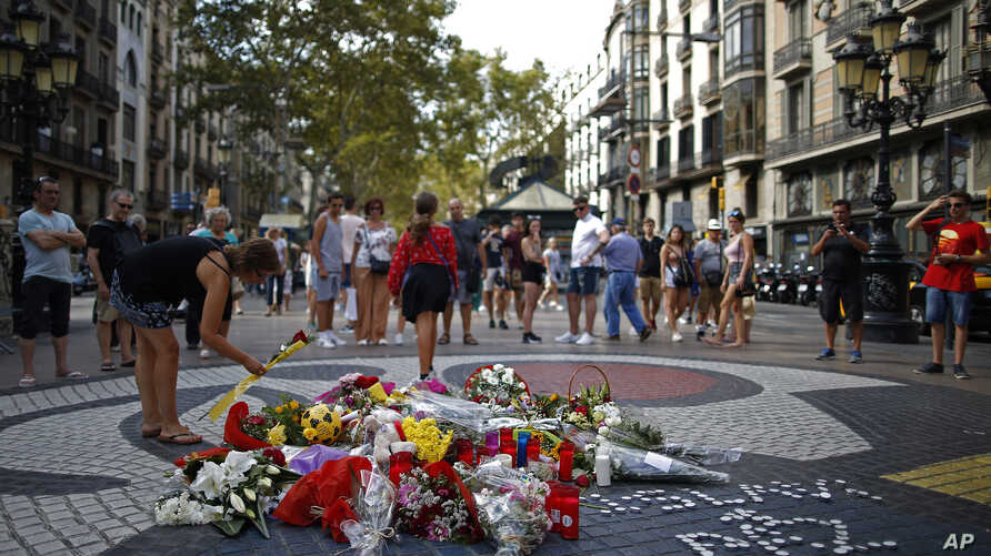 A woman places a flower around a memorial tribute of flowers, messages and candles on Barcelona's historic Las Ramblas in Barcelona, Aug. 16, 2018, the day before to the anniversary of the attacks that took place here on Aug. 17, 2017 killing 16 peop