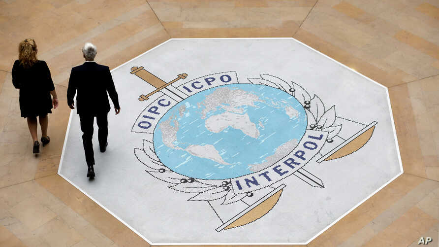 FILE - People walk past the Interpol logo at the headquarters of the international police agency in Lyon, France, Nov.8, 2018.
