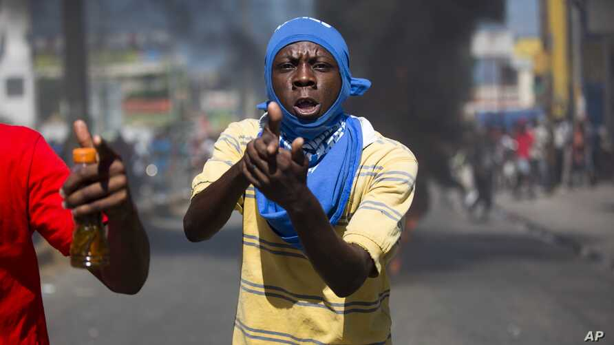 A demonstrator points with his hand making a pistol, during a protest demanding to know how oil assistance  funds have been used by the current and past administrations, in Port-au-Prince, Haiti, Oct. 17, 2018.