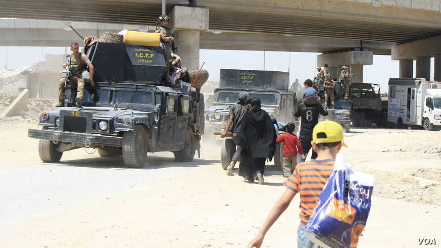 Families take shelter under a bridge where they meet trucks and buses transporting civilians to camps while soldiers travel the opposite direction to the front lines in Mosul, Iraq, June 4, 2017. (H. Murdock/VOA)