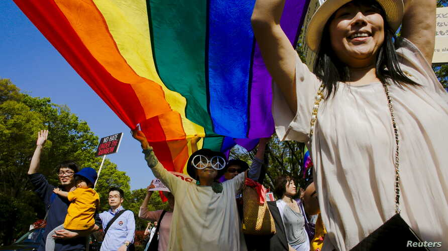 FILE - Participants hold a rainbow flag during the Tokyo Rainbow Pride parade in Tokyo, April 26, 2015. A human rights group said May 6 that Japan has failed to protect its lesbian, gay, bisexual and transgender (LGBT) students.