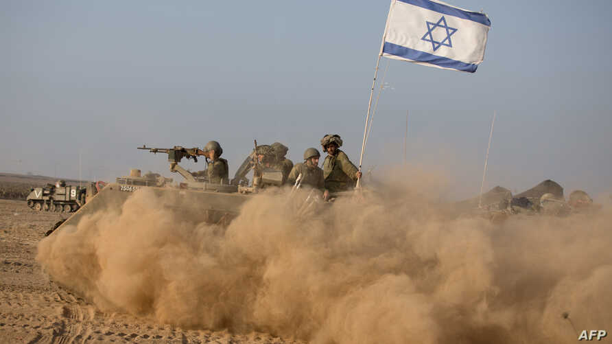Israeli soldiers on an armoured personnel carrier flying an Israeli flag return from the Gaza Strip near Israel's border, July 23, 2014.