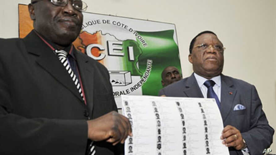 Director of Ivory Coast's Prime Minister Soro's Cabinet Paul Koffi (L) and president of Ivory Coast's Independent Electoral Commission (CEI) Youssouf Bakayoko (R) present the new provisional electoral list ahead of national elections in Abidjan, 12 J
