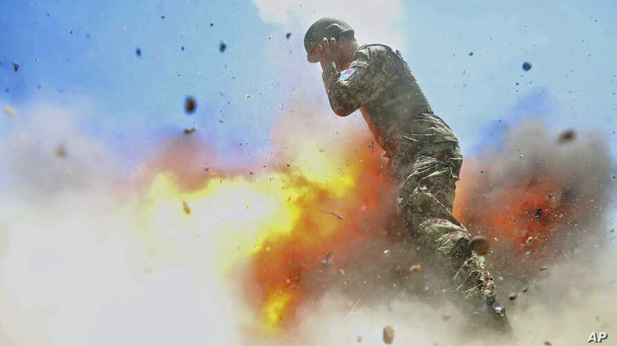 U.S Army combat camera photographer Spc. Hilda Clayton took this photo July 2, 2013 that was released by the U.S. Army, that shows an Afghan soldier engulfed in flame as a mortar tube explodes during an Afghan National Army live-fire training exercis