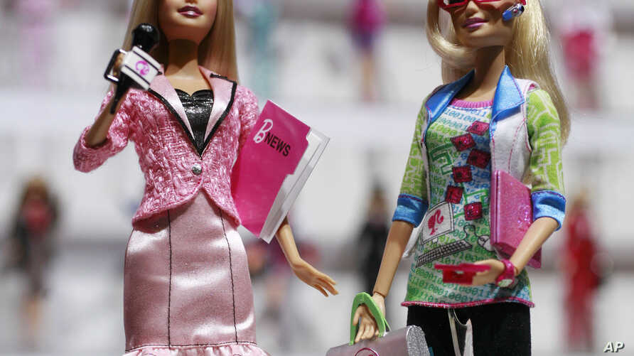 FILE - News anchor Barbie, left, and computer engineer Barbie are arranged for a photo at a New York toy fair. A new study in the journal Science suggests that girls as young as 6 can be led to believe that men are inherently smarter and more talente