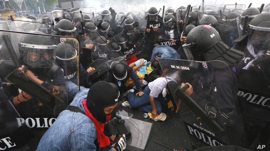 Thai policemen try to arrest anti-government protesters during their clash in Bangkok, Thailand Saturday, Nov. 24, 2012.