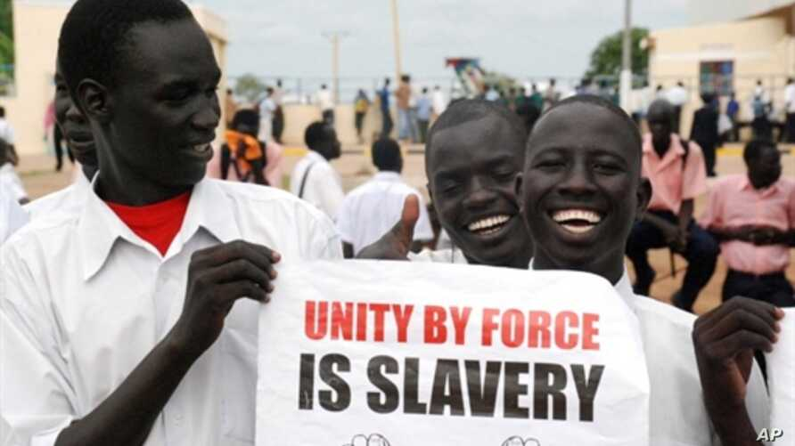 Southern Sudanese men hold a pro-independence poster as they wait for the arrival of envoys from the UN Security Council in Juba, 6 Oct 2010