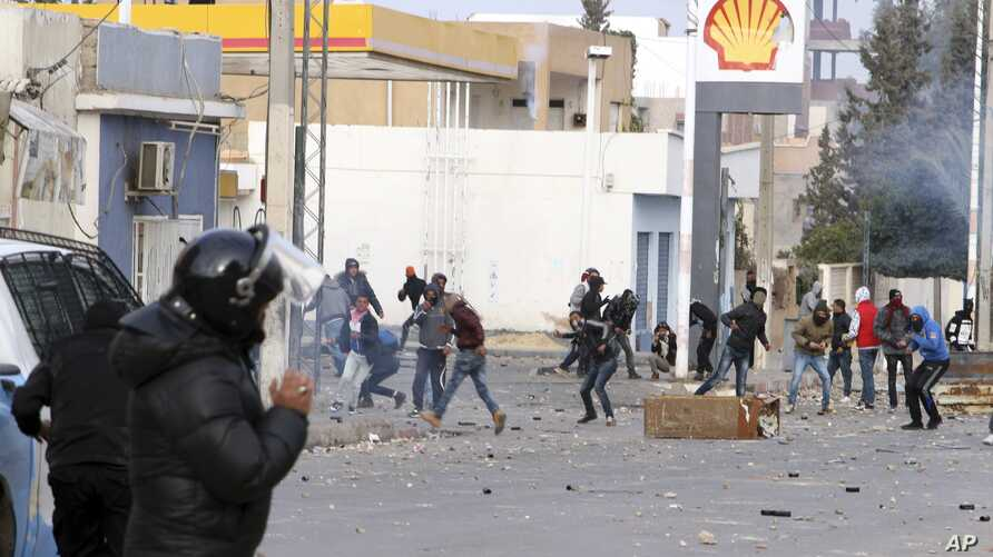 Protesters throw items to police forces in the city of Ennour, near Kasserine, Tunisia, Wednesday, Jan. 20, 2016. Tunisia has declared a curfew in the western city after clashes between police and more than 1,000 young protesters demonstrating for jo