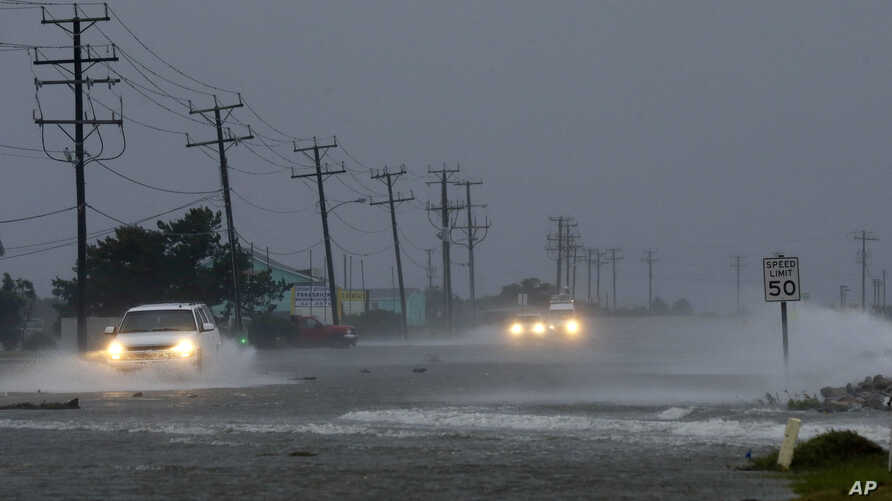 Vehicles navigate a flooded Highway 64 as wind pushes water over the road as Hurricane Arthur passes through Nags Head, N.C., July 4, 2014.