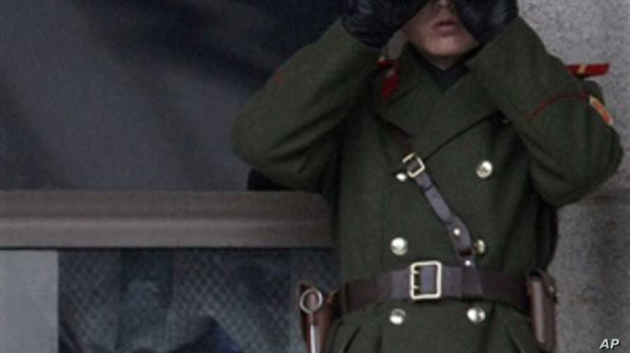 1f73fbd8b4 A North Korean soldier looks at the southern side through telescopes at the  border village of
