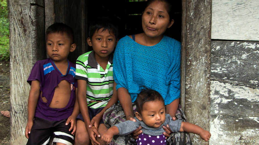 Claudia Maquin, mother of Jakelin Caal Maquin, a 7-year-old girl who died in U.S. custody, stands with her other children outside her house in Raxruha, Guatemala, Dec. 15, 2018.