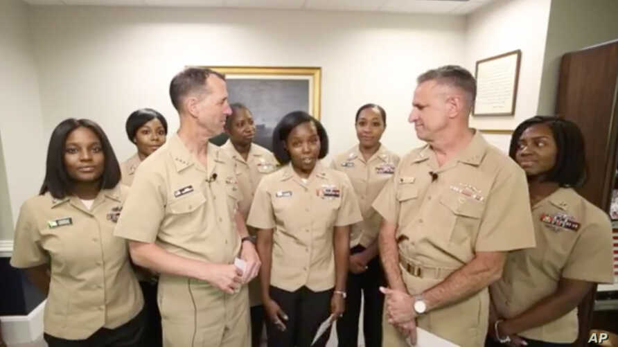 Yeoman First Class LaToya Jones, center, speaks as Chief of Naval Operations Adm. John Richardson, left of center, and Chief of Naval Personnel Adm. Robert Burke, right of center, and other members of the working group listen. The Navy says it will n