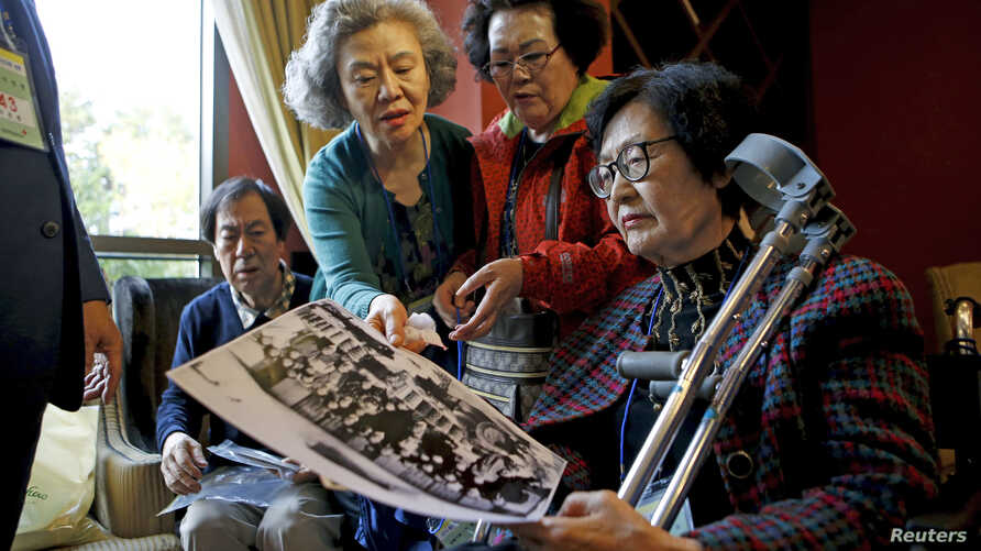 South Korean participants for a reunion check old pictures at a hotel used as a waiting place in Sokcho, South Korea, Oct. 19, 2015.