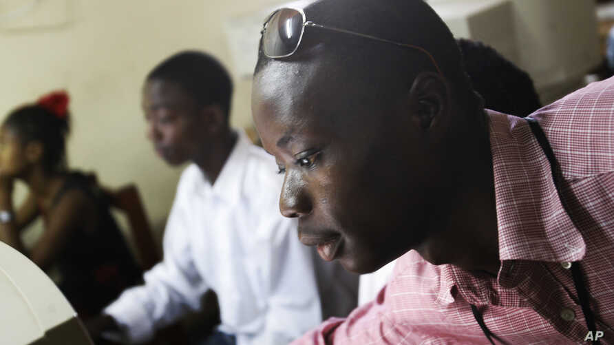 FILE - Momulu Norman, 22, a former child soldier, teaches at a computer school in Monrovia, Liberia.