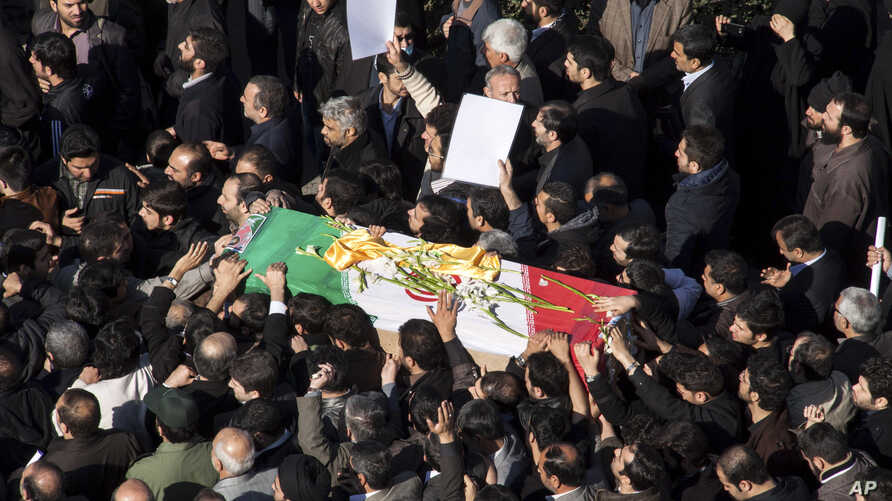 Iranian mourners carry the flag draped coffin of Gen. Hassan Shateri, during a funeral ceremony, in Tehran, Iran, February 14, 2013.