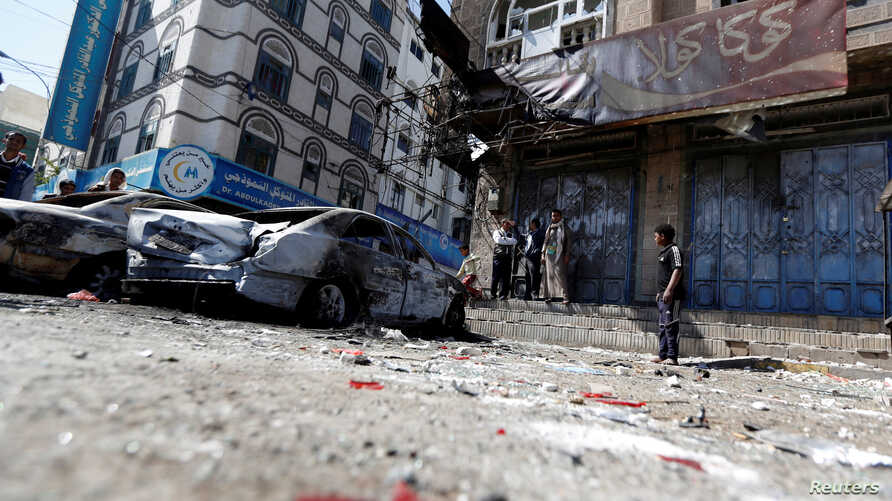 People stand next to damaged cars on a street where Houthi fighters recently clashed with forces loyal to Yemen's former president Ali Abdullah Saleh in Sanaa, Yemen Dec. 5, 2017.
