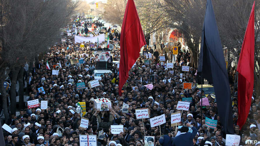 Iranian pro-government supporters march during the funeral of a young member of the Revolutionary Guards, Sajjad Shahsanai, in the city of Najafabad, Jan. 3, 2018. At least three other towns near the cultural hub of Isfahan also saw violence overnigh
