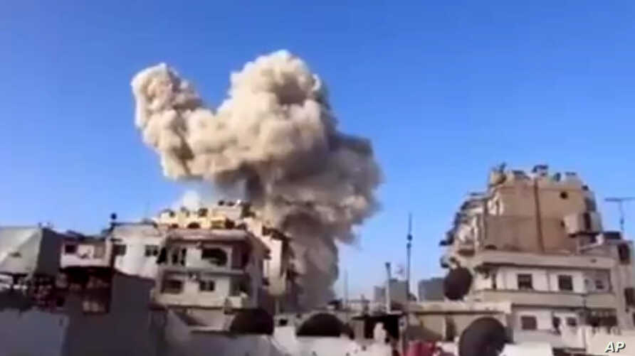 This image taken from video obtained from the Ugarit News shows smoke after a building was struck in a warplane attack in Homs, Syria, November 28, 2012.