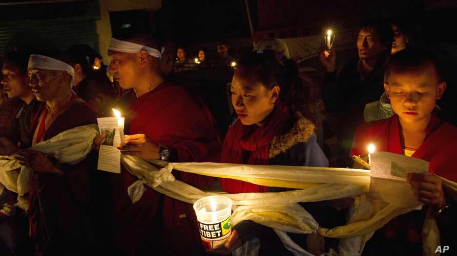 Tibetan exiles participate in a candlelit vigil in solidarity after reports of 52-year-old Tamdrin Dorjee's self-immolation in Tsoe Monastery in northwestern China's Gansu province, in Dharmsala, India, Saturday, Oct. 13, 2012.