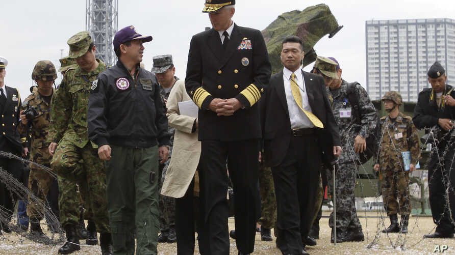 FILE - U.S. Adm. Samuel Locklear talks with Japanese Gen. Shigeru Iwasaki, front left, after inspecting Patriot missile units deployed in Tokyo, April 11, 2012.