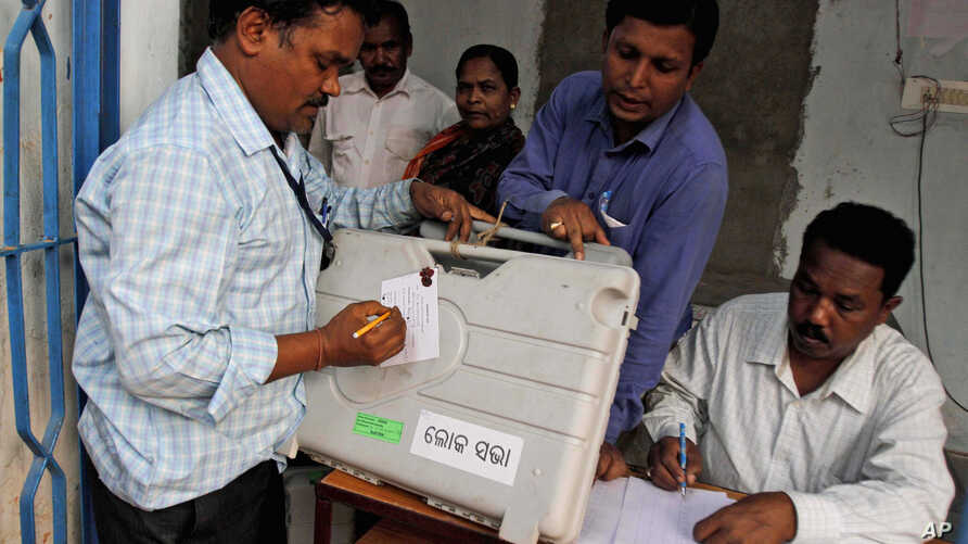 An election officer signs a piece of paper on an electronic voting machine before submitting it at a strong room in Kandhamal district, in the eastern Indian state of Orissa, Thursday, April 10, 2014