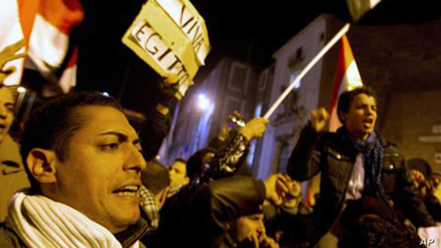 """Demonstrators hold a sign reading """"Long live Egypt"""", top left, and wave Egyptian flags during a protest in support of the Egyptian people, in central Rome, Italy, Monday, Jan. 31, 2011."""