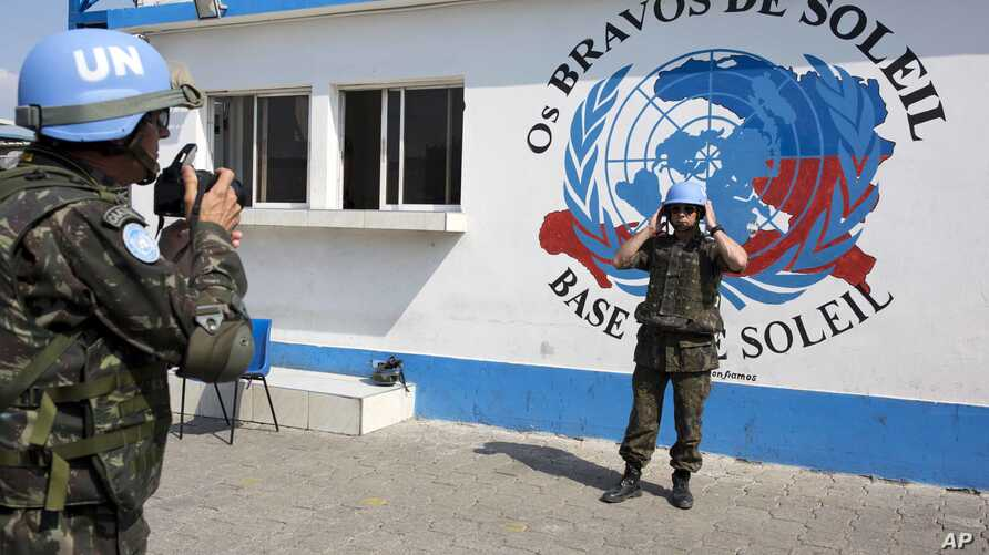 A U.N. peacekeeper from Brazil poses for a souvenir photo before the start of a patrol in the Cite Soleil slum, in Port-au-Prince, Haiti, Feb. 22, 2017.