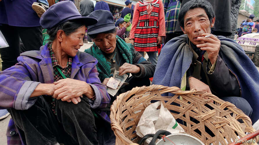 Yi ethnic minority women count money at a local market in Butuo County, Sichuan province, China, July 18, 2017.