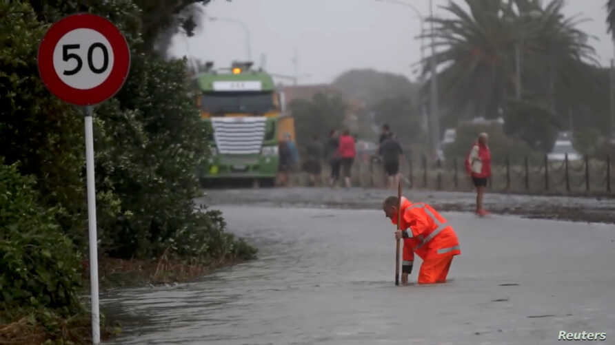 Emergency personnel work on a flooded road in Nelson, after the downgraded tropical cyclone Fehi brought heavy rain in New Zealand, Feb. 1, 2018.