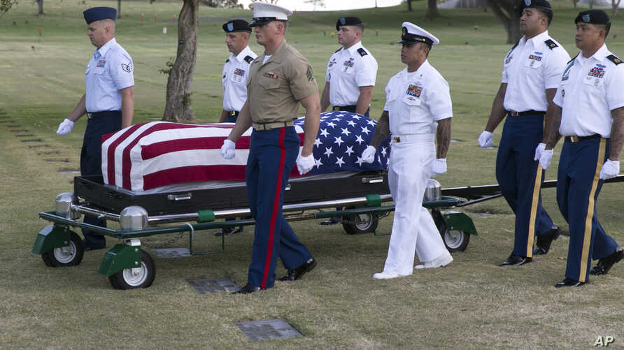 FILE - In this July 27, 2015 file photo, military pallbearers escort the exhumed remains of unidentified crew members of the USS Oklahoma killed in the 1941 bombing of Pearl Harbor that were disinterred from a gravesite at the National Memorial Cemet