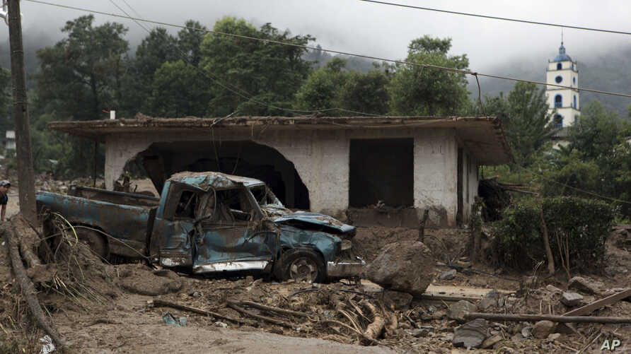 FILE - A pickup lies destroyed next to a house damaged by a mudslide in Xaltepec, on the mountainous north of Puebla state, Mexico, Aug. 7, 2016. The death toll from the remnants of Hurricane Earl grew to more than 30 in Mexico as a new tropical stor