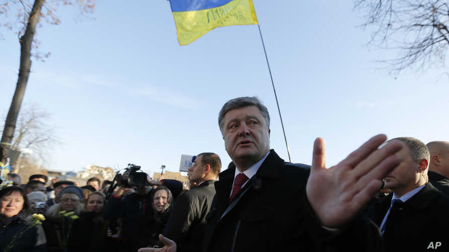 "FILE - Ukraine's President Petro Poroshenko speaks with people after a wreath laying ceremony at the monument to the fallen Heroes of the ""Heavenly Sotnya (Hundred),"" in Kyiv, Ukraine, Nov. 21, 2014."