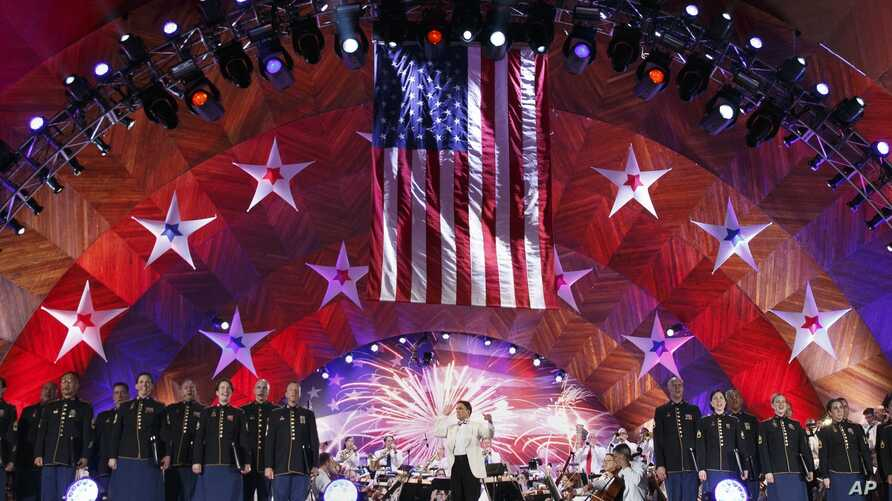 Keith Lockhart, center, conducts The Boston Pops orchestra during rehearsal for the annual Boston Pops Fireworks Spectacular on the Esplanade, July 3, 2017, in Boston.