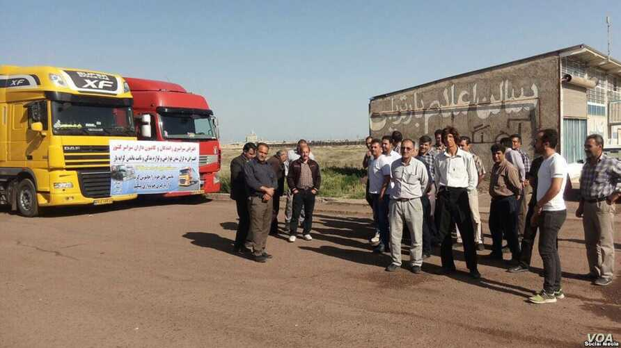 In this image sent to VOA by an Iranian social media user, Iranian truck owners and drivers stage a strike on May 22, 2018, with a sign on their vehicles saying they are upset about increasing costs of road tolls and spare parts while salaries remain