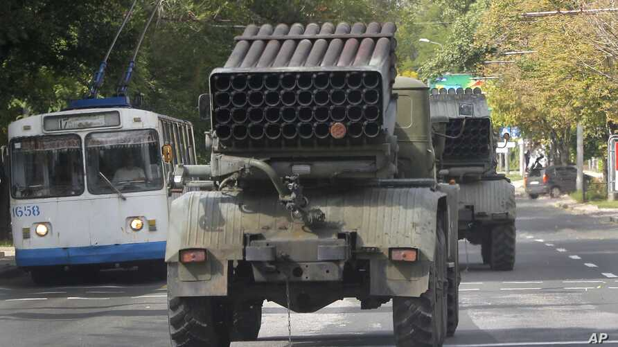 Pro-Russian rebels drive Grad multiple rocket launchers in the town of Donetsk, Ukraine, Sept. 11, 2014. Kyiv accused rebels of sparking recent clashes with tanks and Grad launchers that were among the heavy caliber weapons that were to have been wit