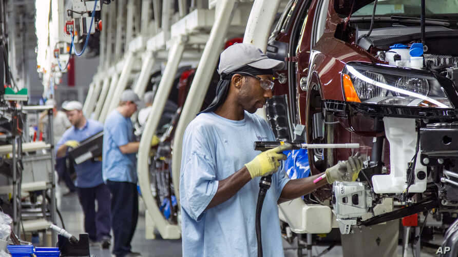 FILE - Employees at the Volkswagen plant in Chattanooga, Tenn., work on the assembly of a Passat sedans, July 12, 2013.