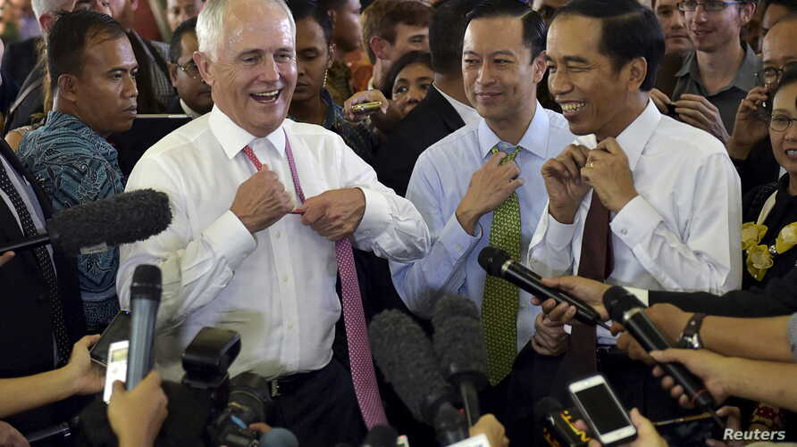 Australian Prime Minister Malcolm Turnbull, left, and Indonesian President Joko Widodo loosen their ties as they visit the Tanah Abang retail market in Jakarta, Nov. 12, 2015.