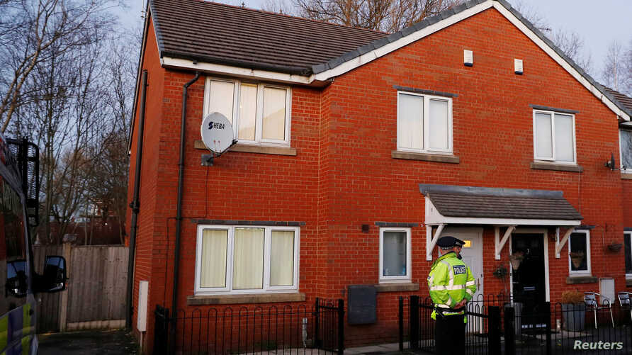 Police officers stand outside a house being searched in connection to a stabbing at Victoria Station in Manchester, Britain, Jan. 1, 2019.