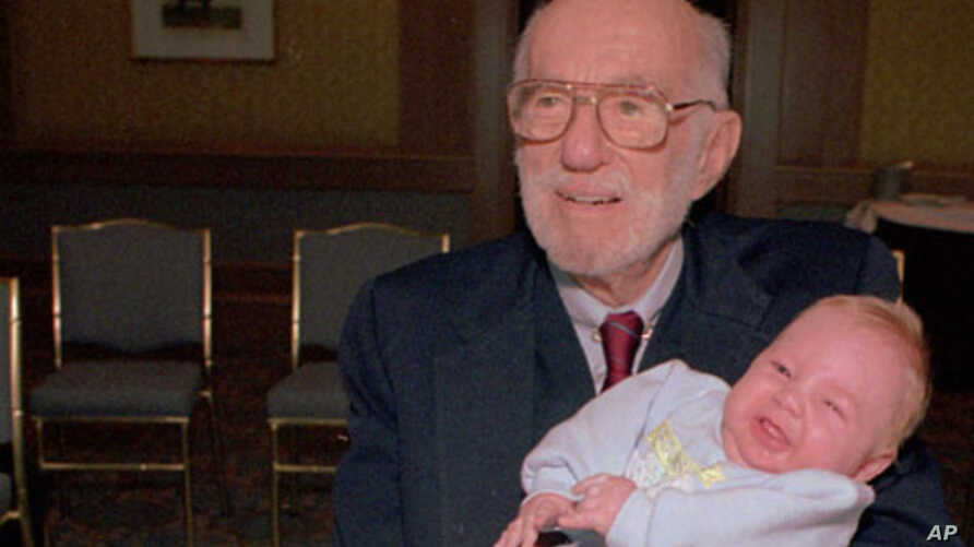 Dr. Spock, 90, holds a baby at a Boston baby fair in April 1993.