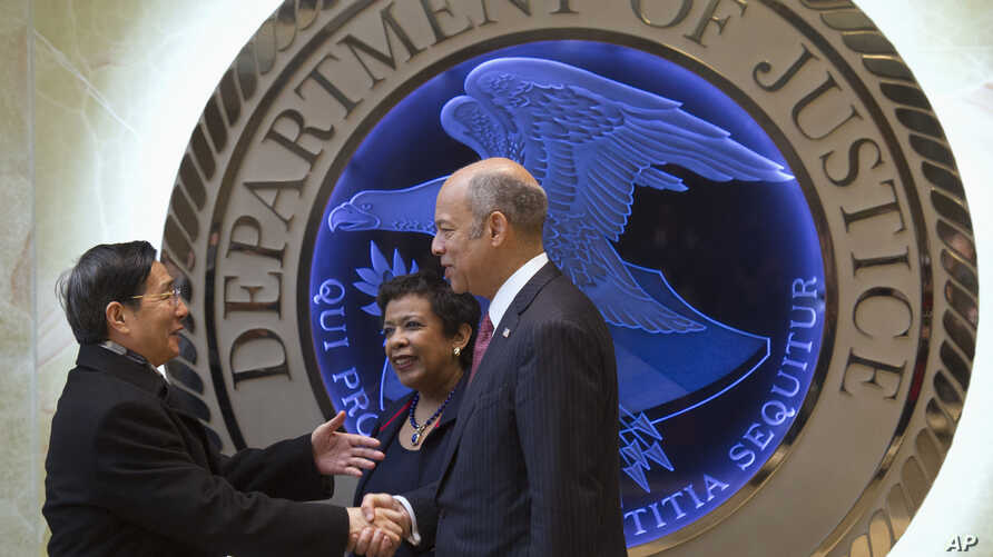 Attorney General Loretta Lynch, center, and Homeland Security Secretary Jeh Johnson, right, welcome Chinese Minister of Public Security Guo Shengkun to the Justice Department in Washington, Tuesday, Dec. 1, 2015.
