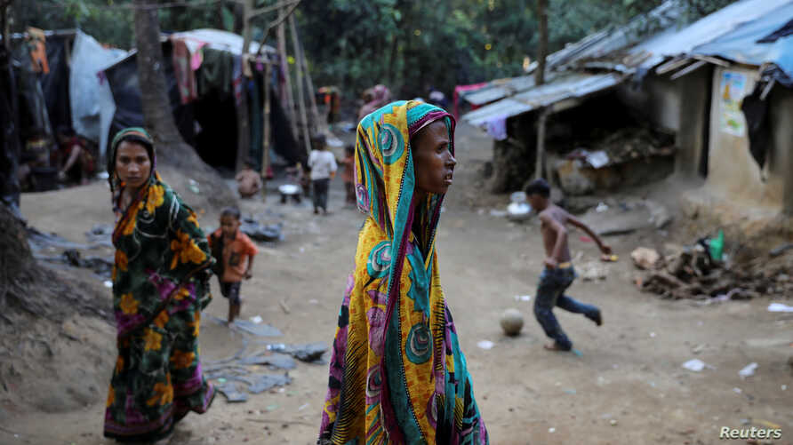 Rohingya Hindu refugees walk through the Kutupalong Hindu refugee camp near Cox's Bazar, Bangladesh, Dec. 17, 2017.